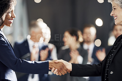 Buy stock photo Cropped shot of two successful business coworkers shaking hands while their colleagues stand and clap behind them in the office