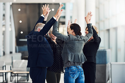 Buy stock photo Cropped shot of a diverse group of successful businesspeople celebrating in the office with a group high five