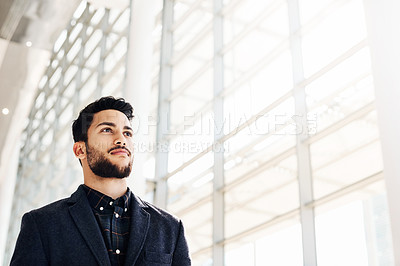 Buy stock photo Low angle shot of a handsome young businessman standing alone in the office during the day