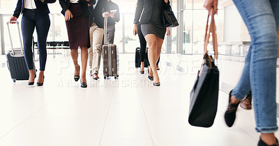 Buy stock photo Cropped shot of a group of businesspeople walking through an airport with heir luggage