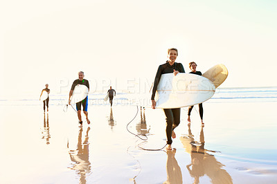 Buy stock photo Full length shot of a happy group of senior people holding their surfboards and walking back to the beach
