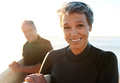 Buy stock photo Cropped portrait of a happy senior couple holding their surfboards and walking towards the beach after their daytime surf