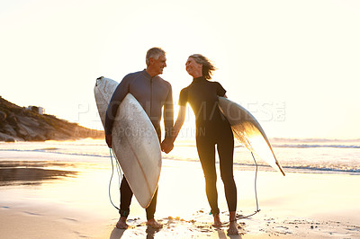 Buy stock photo Full length shot of an affectionate senior couple carrying their surfboards while walking along the beach at sunset