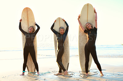 Buy stock photo Full length portrait of three happy senior women standing and posing with their surfboards while on the beach