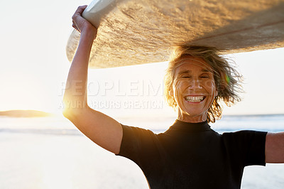 Buy stock photo Cropped shot of a happy senior woman carrying her surfboard over her head after surfing during the day