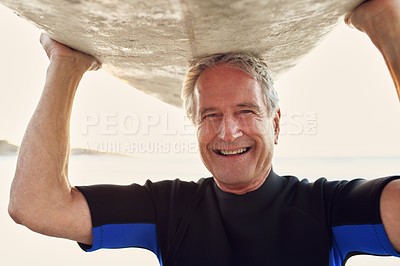 Buy stock photo Cropped portrait of a happy senior man carrying his surfboard over his head after surfing during the day