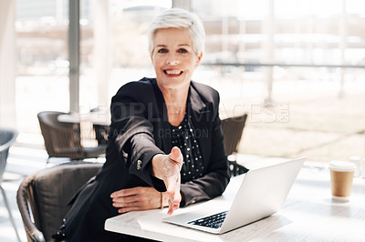 Buy stock photo Portrait of a mature businesswoman extending her arm for a handshake in an airport cafe
