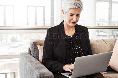 Buy stock photo Shot of a mature businesswoman using a laptop while waiting in an airport