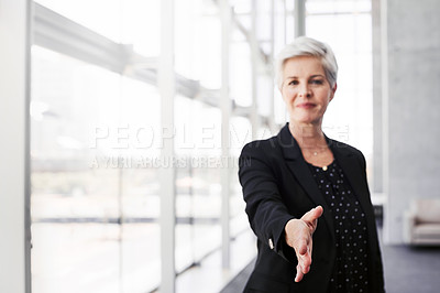 Buy stock photo Portrait of a confident mature businesswoman extending her arm for a handshake in a convention centre