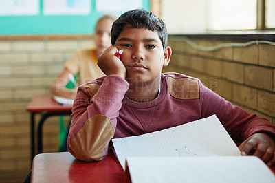 Buy stock photo Shot of a young boy looking bored at his desk in a classroom