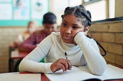 Buy stock photo Shot of a young girl looking bored at her desk in a classroom