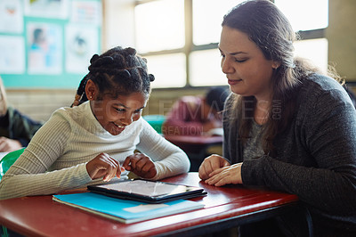 Buy stock photo Shot of a young girl using a digital tablet during a lesson with her teacher