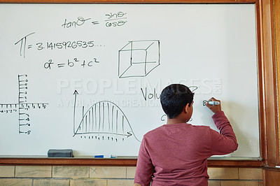 Buy stock photo Rearview shot of a young boy standing writing mathematics symbols on a board in a classroom