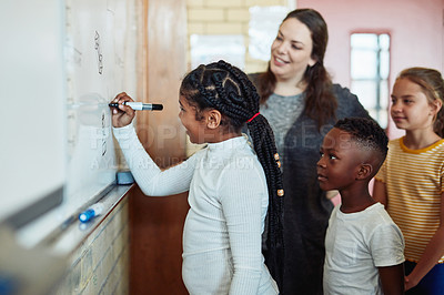 Buy stock photo Shot of a group of young children writing on a board during a lesson with their teacher in a classroom