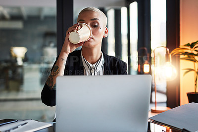 Buy stock photo Shot of an attractive young businesswoman drinking coffee and using a laptop while working late in her office
