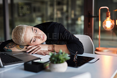 Buy stock photo Shot of an attractive young businesswoman sleeping on a desk while working late in her office