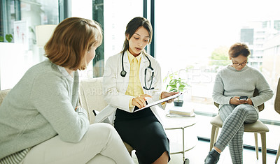 Buy stock photo Shot of a doctor having a discussion with her patient in the waiting room of a clinic