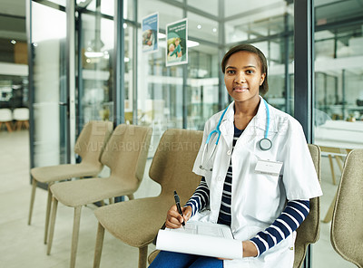 Buy stock photo Shot of a young doctor sitting in the waiting room of a clinic