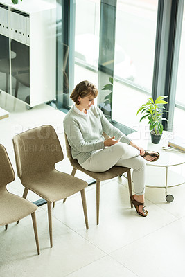 Buy stock photo Shot of a young woman using a smartphone while sitting in the waiting room of a clinic