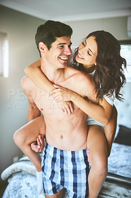 Buy stock photo Shot of a playful young couple spending quality time together in their bedroom at home