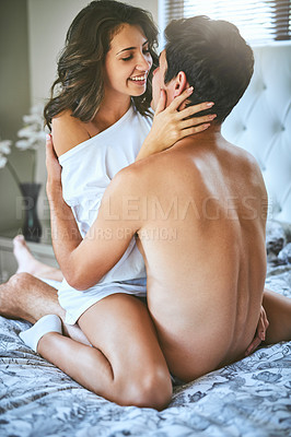 Buy stock photo Shot of an affectionate young couple sharing an intimate moment in their bedroom at home