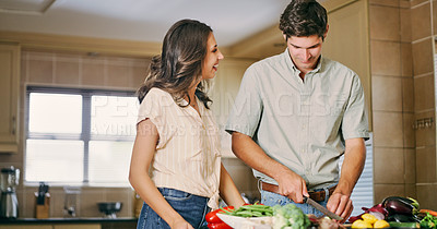 Buy stock photo Shot of a young couple cooking together in the kitchen at home