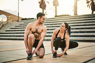 Buy stock photo Shot of two sporty young people tying their shoelaces while exercising together outdoors