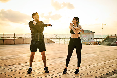 Buy stock photo Shot of two sporty young people exercising together outdoors