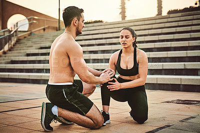 Buy stock photo Shot of a sporty young woman suffering from an injury while exercising with her partner outdoors