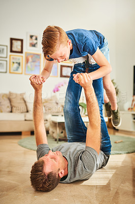 Buy stock photo Full length shot of a father playing with his son on the floor at home