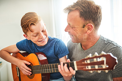 Buy stock photo Shot of a father teaching his son how to play the guitar at home