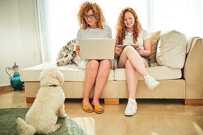 Buy stock photo Full length shot of a mother and daughter along with their adorable dog relaxing together at home