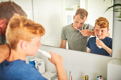 Buy stock photo Shot of a father and son brushing their teeth together in the bathroom at home