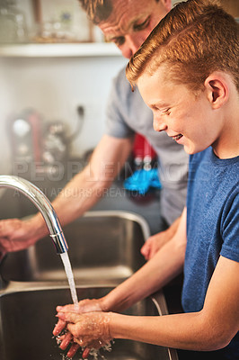 Buy stock photo Shot of a father helping his son wash his hands in the kitchen at home