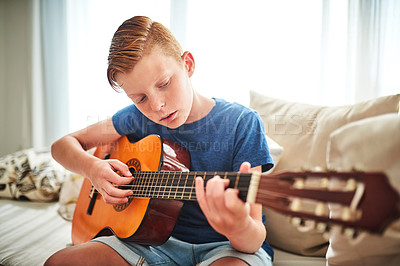 Buy stock photo Shot of a handsome teenage boy playing the guitar while sitting on a couch at home