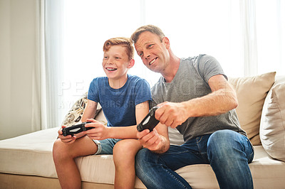 Buy stock photo Shot of a cheerful father and son playing video games together at home