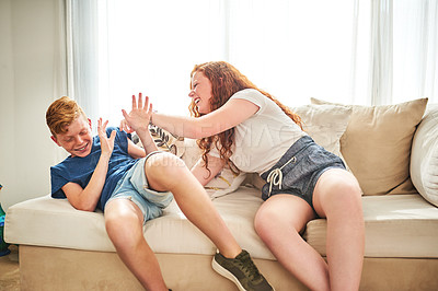 Buy stock photo Shot of a cheerful teenage brother and sister playing together while sitting on a couch at home