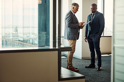 Buy stock photo Full length shot of two businesspeople going over some paperwork together in an office