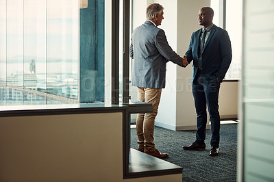 Buy stock photo Full lengths shot of two businessmen shaking hands in an office
