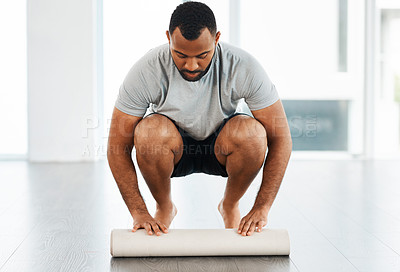 Buy stock photo Full length shot of a handsome young man rolling out his yoga mat inside a studio
