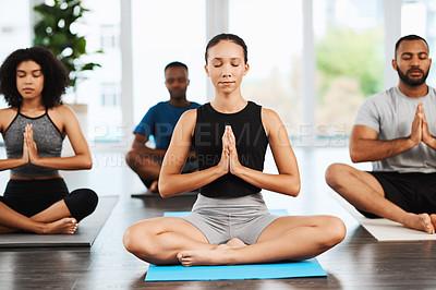 Buy stock photo Full length shot of a group of young people sitting down and meditating while doing yoga together inside a studio