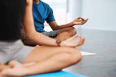 Buy stock photo Shot of a group of unrecognizable people sitting down and meditating while doing yoga inside a studio