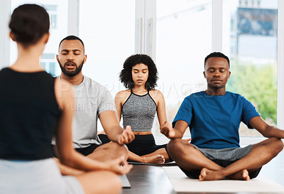 Buy stock photo Shot of a group of young people sitting down and meditating while doing yoga inside a studio