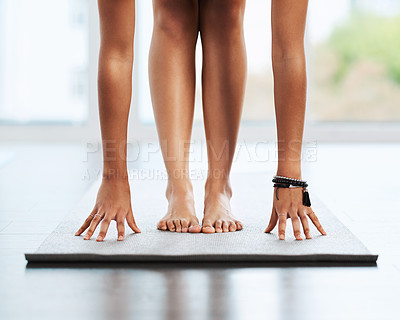 Buy stock photo Shot of an unrecognizable woman doing her stretches while practicing yoga indoors