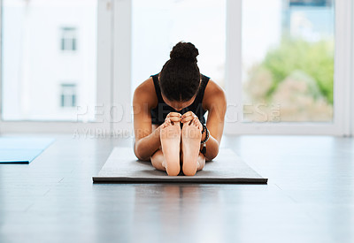 Buy stock photo Full length shot of a young woman sitting down and doing her stretches while practicing yoga inside a studio