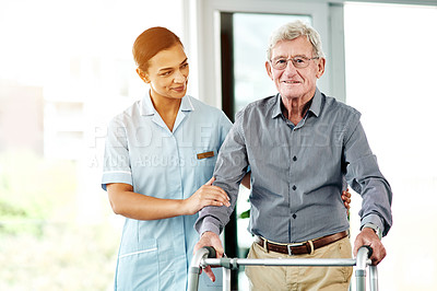 Buy stock photo Shot of a young nurse helping a senior man with a walker