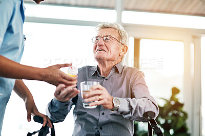 Buy stock photo Shot of a nurse giving a senior man his medication to take with a glass of water