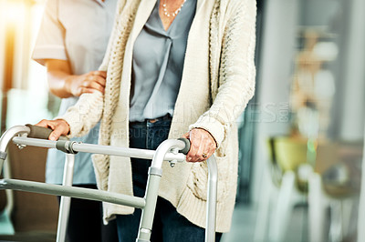 Buy stock photo Cropped shot of a nurse helping a senior woman with a walker