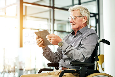 Buy stock photo Shot of a senior man in a wheelchair using a digital tablet