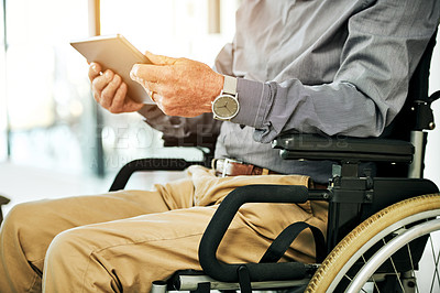 Buy stock photo Cropped shot of a senior man in a wheelchair using a digital tablet